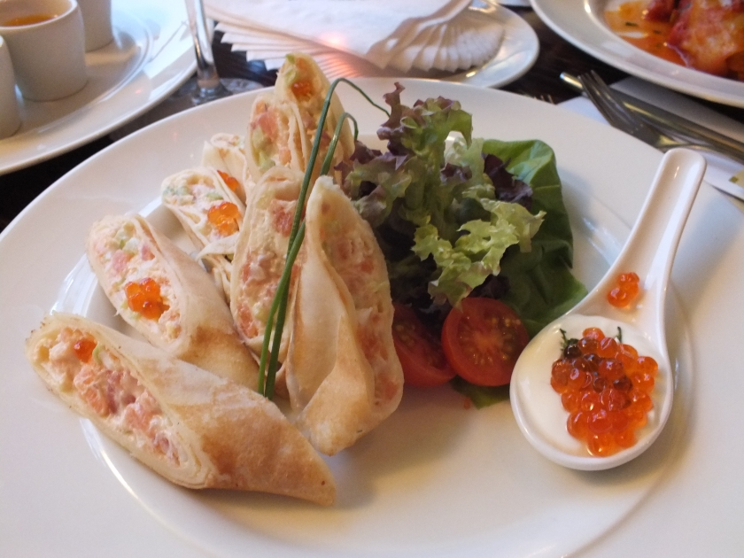Salmon tartar and cream cheese in a blini with red caviar.