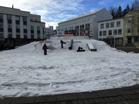 A large pile of snow in the middle of town set up for snowboarders.